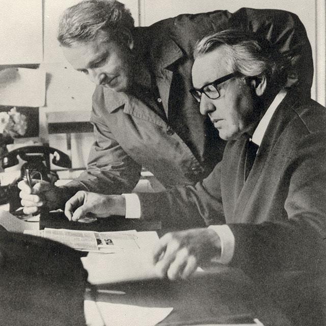 Foto: Wolfgang Wagner beugt sich stehend zu seinem Bruder Wieland, der am Schreibtisch sitzt