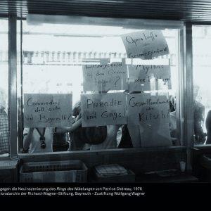 """Foto: Menschen halten von außen Transparente an die Fensterfront des Kartenbüros des Festspielhauses, um gegen die Neuinszenierung des """" Ring des Nibelungen"""" von Patrice Chéreau zu protestieren, 1976"""