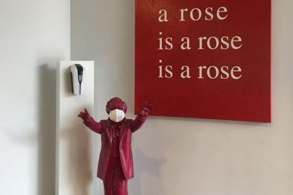 """Foto: Skulptur Richard Wagner mit FFP2-Maske und Desinfektionsmittelspender, im Hintergrund """"Gedanken-Bilder. Gertrude Stein"""" von rosalie, 2002, atelier rosalie, Stuttgart © Nationalarchiv der Richard-Wagner-Stiftung, Bayreuth"""